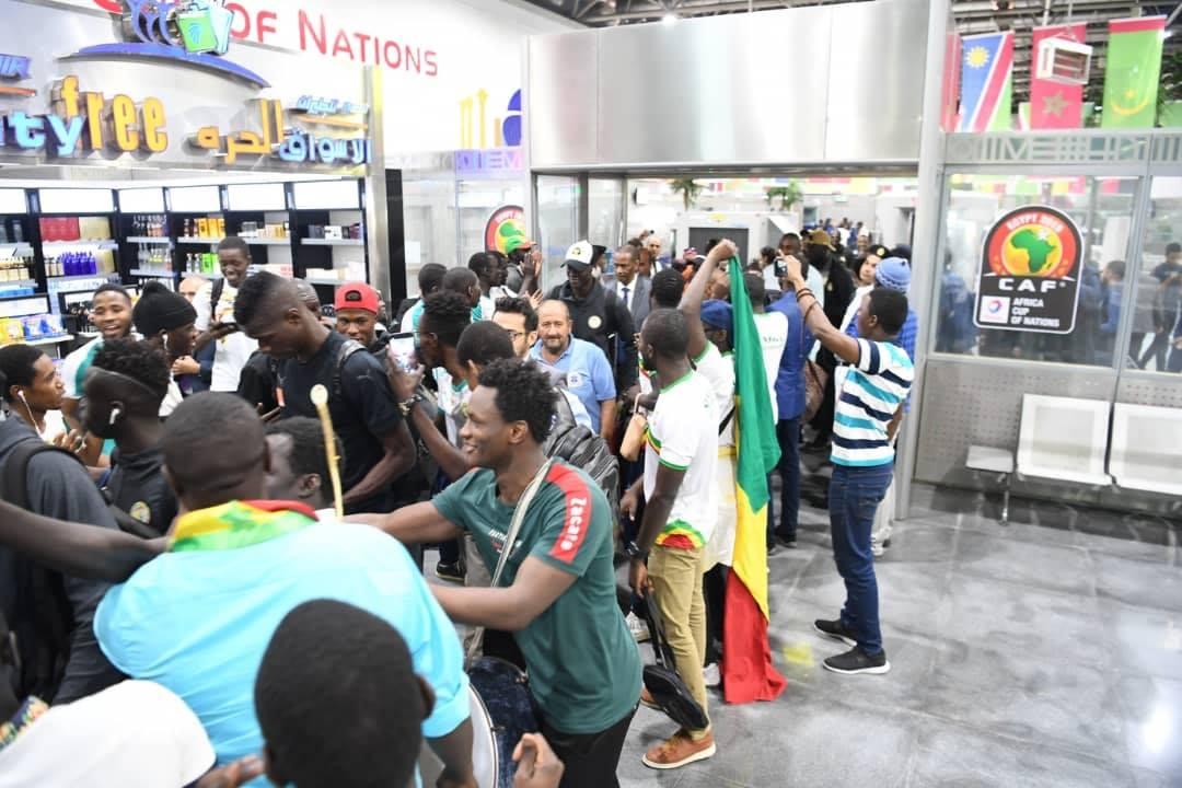 Can 2019: Les Lions bien arrivés en Égypte (photos) - Un groupe de personnes debout devant un magasin - Foule