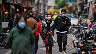 People wearing face masks walk on a street in Wuhan, China's central Hubei province on April 14, 2020. - China has largely brought the coronavirus under control within its borders since the outbreak first emerged in the city of Wuhan late last year. (Photo by Hector RETAMAL / AFP) (Photo by HECTOR RETAMAL/AFP via Getty Images)