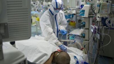 This photo taken on February 22, 2020 shows a nurse checking a patient in an intensive care unit treating COVID-19 coronavirus patients at a hospital in Wuhan, in China's central Hubei province. - China on February 26 reported 52 new coronavirus deaths, the lowest figure in more than three weeks, bringing the death toll to 2,715. (Photo by STR / AFP) / China OUT