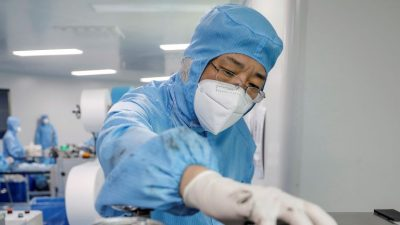 Beijing (China), 29/04/2020.- A worker wearing a protective suit and a face mask produces masks at a factory of the Naton Technology Group in Beijing, China, 29 April 2020, amid the ongoing coronavirus COVID-19 pandemic. Established in 1996, the Naton Technology Group in Beijing's Haidian district previously manufactured surgical orthopedic products to hospitals across China. It has been involved in protective face mask production since February 2020 and so far it can produce about five million face masks per day. EFE/EPA/WU HONG