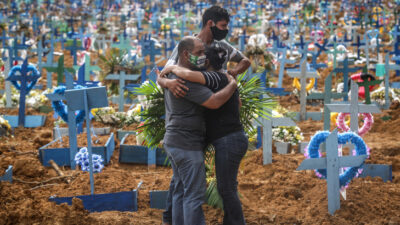 MANAUS, BRAZIL - MAY 19: Relatives of a deceased person wearing protective masks mourn during a mass burial of coronavirus (COVID-19) pandemic victims at the Parque Taruma cemetery on May 19, 2020 in Manaus, Brazil. Brazil has over 260,000 confirmed cases and more than 17,000 deaths caused by coronavirus (COVID-19) pandemic. (Photo by Andre Coelho/Getty Images)